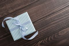 Striped gift box with blue ribbon stock photos