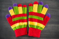Striped gloves. Colorful striped gloves on grey background Royalty Free Stock Photos