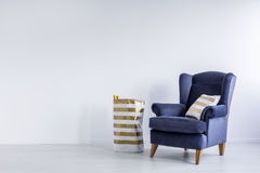 Gold pillow on blue armchair Stock Photo