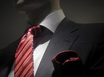 Striped grey jacket with red striped tie and handk. Close-up of a dark grey striped jacket with white shirt, striped red tie and red handkerchief royalty free stock images