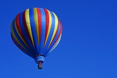 Striped Hot Air Balloon. A colorfully striped hot air balloon floats in a clear blue sky Royalty Free Stock Photography