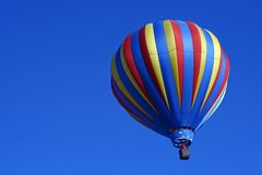 Striped Hot Air Balloon. A colorfully striped hot air balloon floats in a clear blue sky Stock Image