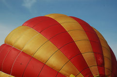 Striped hot air balloon. Red and yellow striped hot air balloon envelope with blue sky background Royalty Free Stock Photography