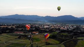 Striped hot air balloon flying over earth, evening landscape and city with little houses, a river in Laos Vang Vieng stock video footage
