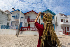 Striped houses in Costa Nova. Young woman with blond dreadlocks makes a photo on a smartphone. Stock Photos