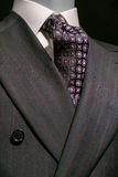 Striped Jacket and Patterned Tie (Vertical). Close up of a dark gray striped jacked with white shirt and patterned black & purple tie Stock Photo