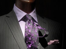 Striped jacket with purple shirt & tie. Close-up of a dark grey striped jacket with purple shirt, patterned tie and handkerchief Royalty Free Stock Photos