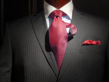 Striped jacket with red striped tie. Close-up of a dark grey striped jacket with blue striped shirt with white collar, striped red tie and red handkerchief Stock Photography