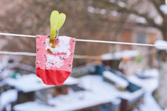 The striped kids sock is hanged on a wire with peg in winter. The striped kids sock is hanged on a wire with a peg in winter. cold day, washing line in the stock photos