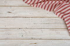 Striped kitchen napkin in the corner of wooden planks background Royalty Free Stock Photography