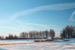 Striped landscape - ice on the river, boat station and blue sky Royalty Free Stock Images