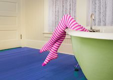 Striped legs over colorful antique bath tub Royalty Free Stock Photos