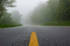 Striped Lines on a Road in the Fog Royalty Free Stock Images