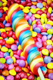 Striped lollipop and smarties Royalty Free Stock Photos
