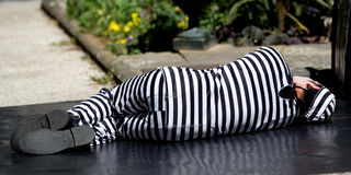 Striped man lying on the ground Royalty Free Stock Image