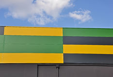 Striped metal facade. Colorful striped facade of a modern building with a blue sky Stock Photography