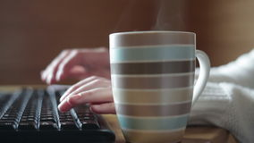 Striped mug of coffee on the table and keyboard. Close up stock video
