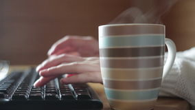 Striped mug of coffee on the table and keyboard stock footage