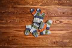 Striped multicolored knitted baby socks on a wooden background stock photos