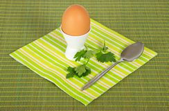 Striped napkin, boiled egg and spoon Stock Photography