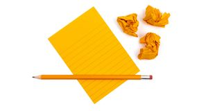 A striped notebook with orange sheets next to which lies a sharpened pencil and three crumpled pieces of paper on white background. Mock up with copy space for royalty free stock photos