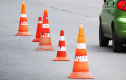 Striped orange cones and car fragment Stock Photography