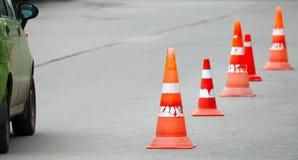 Striped orange cones on the road. Striped orange cones on the asphalt road Stock Images