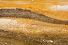 Striped orange limestone in hot pool, Yellowstone Park, Wyoming. Royalty Free Stock Photos
