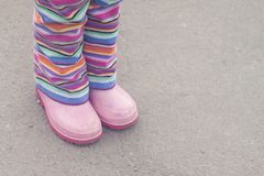 Striped pants and pink boots. Little girl showing her striped pants and her pink rain boots Royalty Free Stock Photography