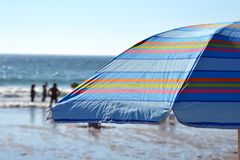 Striped parasol on the beach. Beach with an open parasol and sea Stock Photography