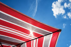 Striped parasol. Red whitw and gray striped parasol during summer holidays Royalty Free Stock Photography