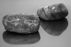 Striped pebbles on a dark glossy background Stock Photography