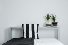 Striped pillow on black and white coverlet Royalty Free Stock Image