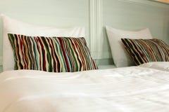 Striped pillow on a white bad Royalty Free Stock Photos