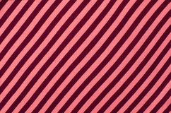 Striped pink and red textile pattern as a background. Close up on diagonal stripes material texture fabric Stock Image