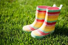 Striped rain boots on grass Royalty Free Stock Images