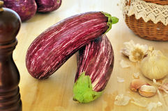 Striped raw eggplants. Striped raw eggplant purple color laid on a kitchen cutting board Stock Photo