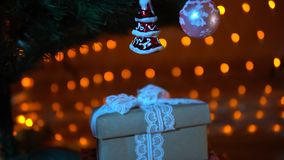 Gifts under a christmas tree against a background of garland at night, close-up. Striped red green gift boxes, beige gift with a white guipure bow under a stock footage