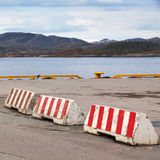 Striped red and white concrete road barriers Royalty Free Stock Photo