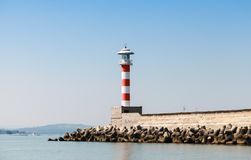 Striped red and white lighthouse tower. Stands on the entrance pier in port of Burgas, Black Sea coast, Bulgaria Royalty Free Stock Image