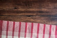 Striped red and white napkin on an old wooden brown background, top view. Image with copy space. Kitchen table with a towel - top Royalty Free Stock Photos