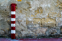 Striped red and white pole against a textured wall Stock Image