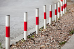 Striped red and white signal poles on roadside Royalty Free Stock Photo
