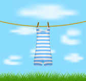 Striped retro swimsuit hanging on rope Stock Photos