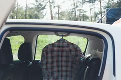 Striped shirt hanging in the car. Prepared shirt in white car royalty free stock images