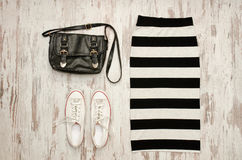 Striped skirt, black bag and white sneakers. Fashionable concept.  Royalty Free Stock Photos