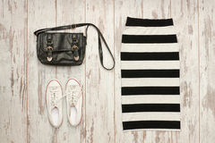Striped skirt, black bag and white sneakers. Fashionable concept.  Stock Photos