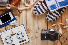 Striped slippers, camera, bag and maritime decorations on the wooden background Stock Images