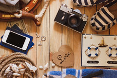 Striped slippers, camera, phone and maritime decorations, background. Striped slippers, camera, phone and maritime decorations on the wooden background, top view Stock Photo