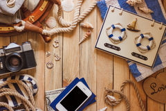 Striped slippers, camera, phone and maritime decorations, top view Royalty Free Stock Photos